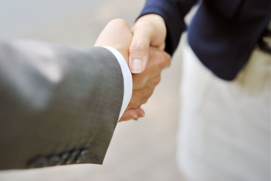Employment lawyer shaking hands with businessman